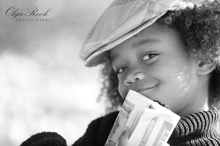 Nostalgic black and white portrait of a small curly boy wearing a cap and holding a newspaper. He is smiling impishly and his eyes are lauging!