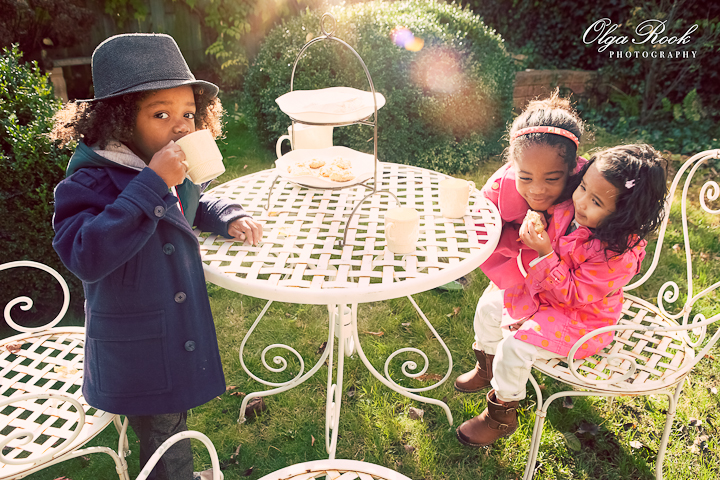 Photo of three little children havind a high tea party in a garden. Bold colors and sun flair make the image look almost magical.