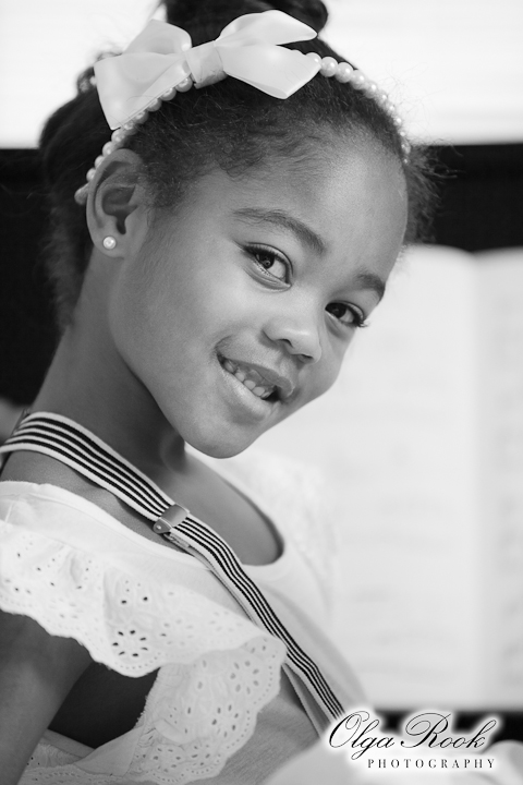 Black and white portrait of a small black girl. She is elegantly dressed, smiles and looks like a ballerina.