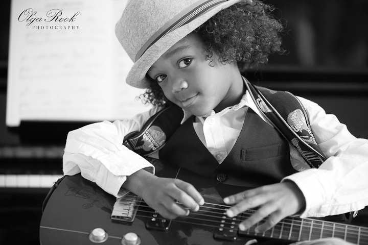Classic retro style portrait of a small black boy with a guitar. The boy is wearing a hat and looks into the lens with an ironic expression.
