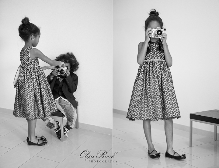 Black and white photos of an elegantly dressed small girl with a camera.