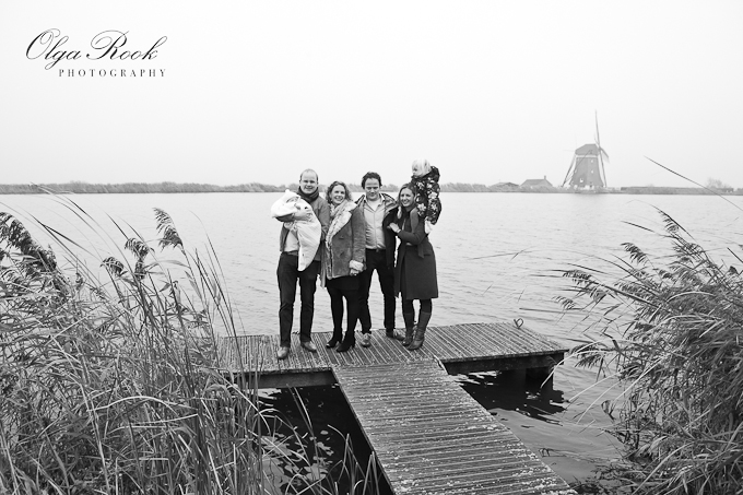 Black and white outdoor family portrait: two couples and two little children standing next to a lake with a Dutch windmill in the background.