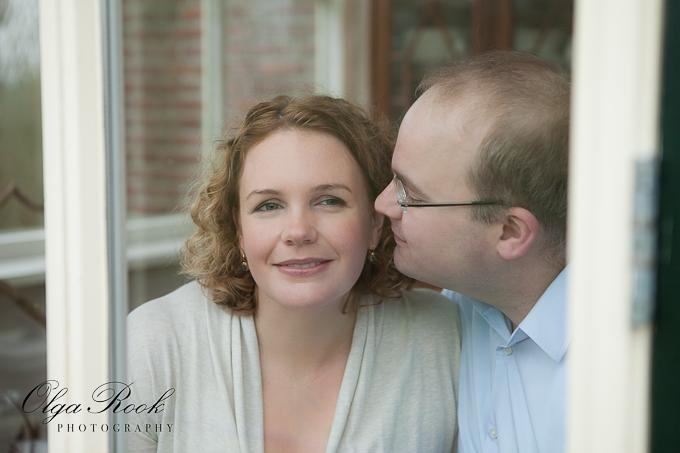 Foto van een stel achter de raam: de man wil zijn vrouw een zoen op haar wang geven.