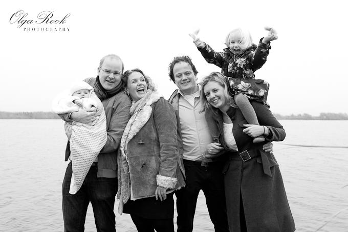 Zwartwit familieportret: vier volwassenen en twee kleine kinderen, iedereen vrolijk en lachend.