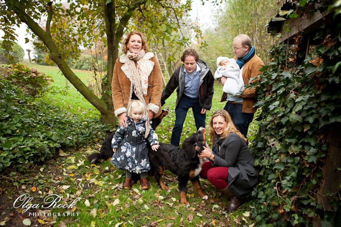 Kleurrijke familiefoto: twee vrouwen, twee mannen, een klein meisje, een baby en twee honden in de tuin. Spontane uitdrukkingen, relaxte niet geposeerde houding, gelukkig lachen - een perfecte familiefoto met veel interactie..