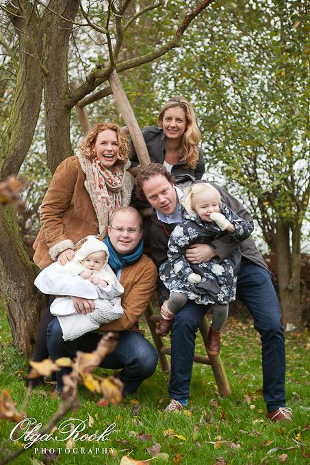 Kleurenfoto van twee gelukkige gezinnen met twee kleine kinderen in de herfsttuin.