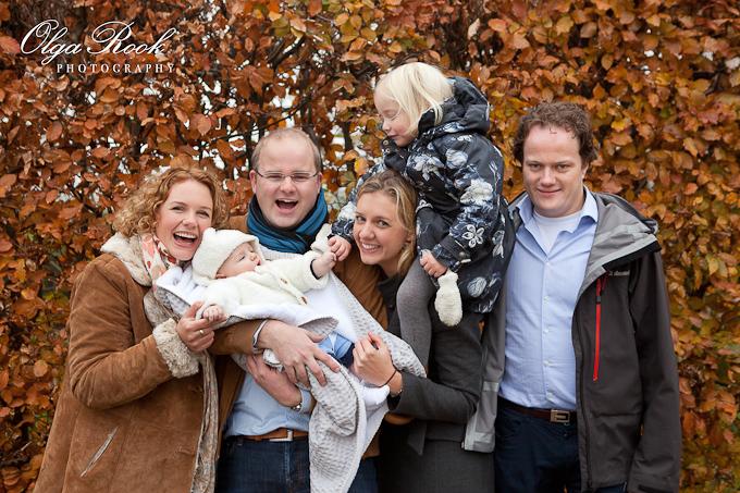 Kleuren familiefoto: twee leuke gezinnen met een baby en een klein meije. Iedereen lacht.