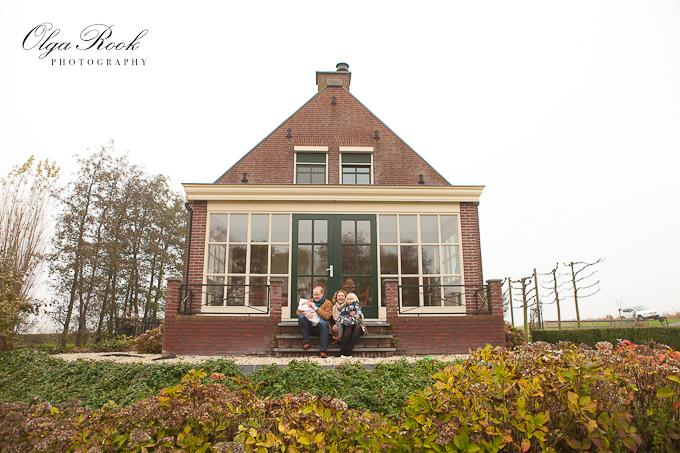 Foto van een gezin op de trappen van een mooi landhuis.
