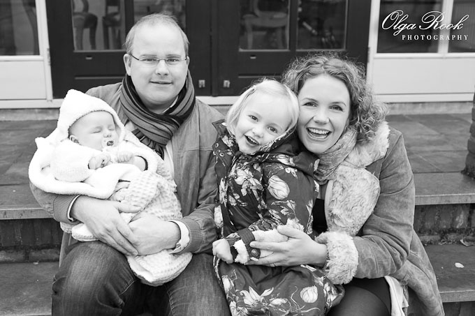 Zwartwitte gezinsportret: een man, zijn vrouw en twee kinderen: een baby en een klein blond meisje.