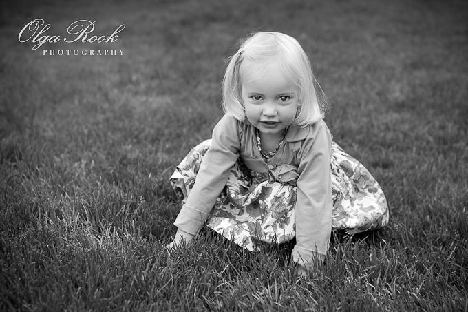 Zwartwit portret van een klein blond meisje. Ze zit in de gras.