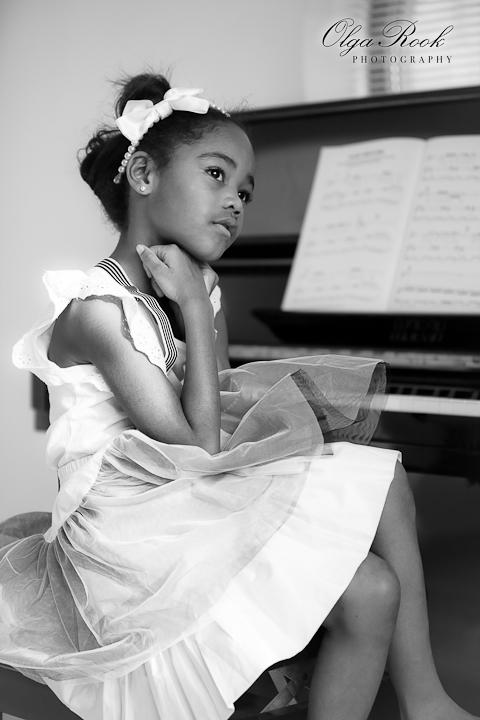 Klassieke zwartwit foto van een klein donker meisje achter de piano. Ze draagt mooie elegante kleren en heeft een dromerige romantische blik.
