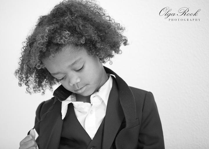 Modeachtige zwartwit portret van een kleine krullerige donkere jongentje met een chique pakje.