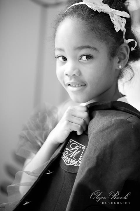 Zwartwit modefoto van een klein donker meisje.