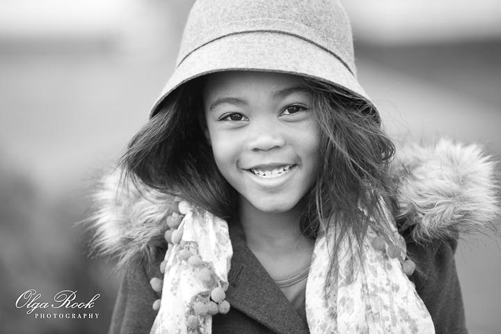 Kinderportret die laat denken aan modefotografie: een klein lachend meisje met een fancy hoedje.