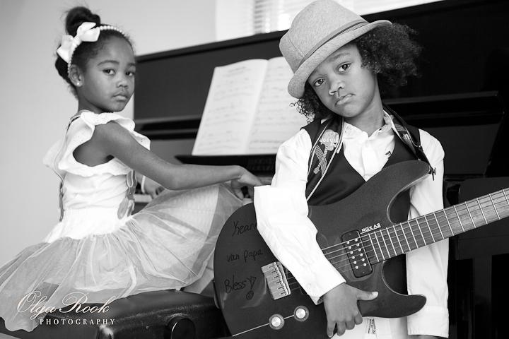 Zwartwit foto van kleine zusje en broerje: de jongen heeft een echte electrische gitaar en het meisje zit achter de piano.