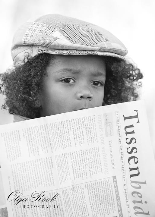 Zwartwit nostalgisch portret van een kleine jongentje met een krant en een petje.