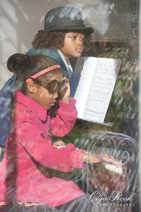 Kleurenfoto van een zusje en haar kleine broerje achter de piano. De kinderen kwamen net naar binnen en hebben nog hun jassen aan.