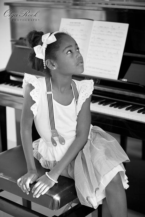 Klassieke zwartwit foto van een klein meisje achter de piano. Het meisje draagt mooie chique kleren en kijkt omhoog.