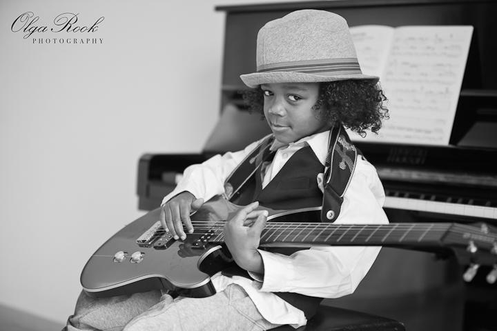 Zwartwit portret van een klein krullerig jongentje met een electrische guitar en een hoed.