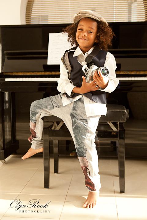 Kleurenfoto van een kleine krullerige donkere jongentje met een fototoestel in zijn handen. De jongen draagt klassieke kleren en een petje en heeft blote voeten. Warme kleuren, het sfeer en een piano achter de jongen laten denken aan de jaren twintig-dertig.