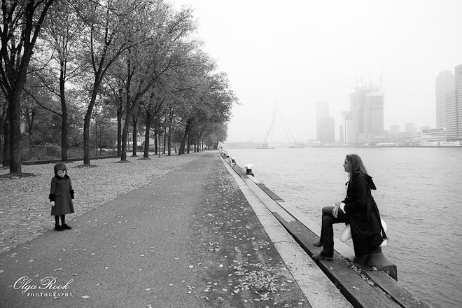 Foto van een moeder en een kind die op de kade naast de Maas wandelen.