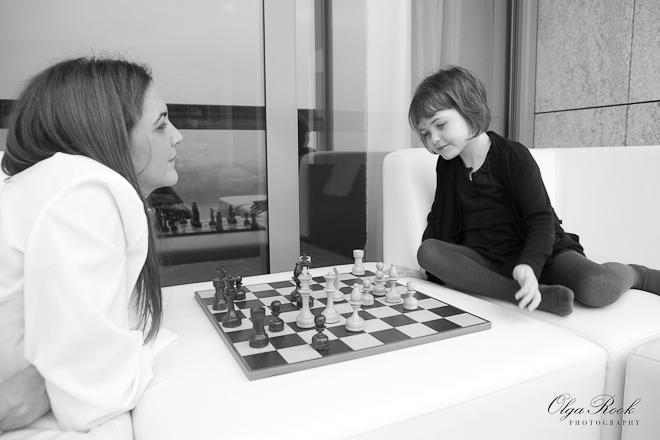 Foto van een moeder die haar klein dochtertje leert schaak te spelen.