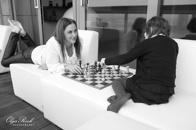 Foto van een moeder en haar klein dochtertje die schaak spelen op balkon.