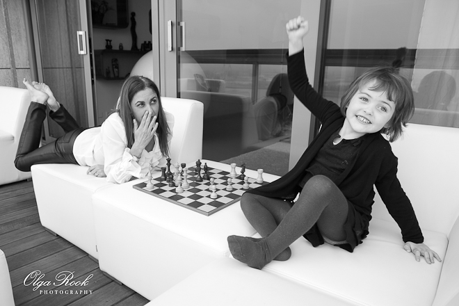 Foto van een moeder en een klein meisje op balkon. Ze spelen schaak en het kind is jubelend dat ze heeft gewonnen.