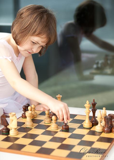 Kleurenfoto van een klein meisje in balletjurk die zit met zichzelf schaak te spelen.