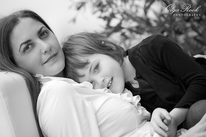 Black and white portrait of a beautiful lady with dark hair and dark eyes lying on a sofa on a balcony. Her daughter is leaning on her mother's breast. The photo is serene, dreamy and romantic.