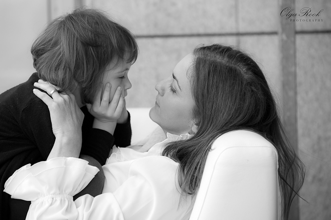 A romantic photograph of a mother and child lying on a sofa, looking at each other.