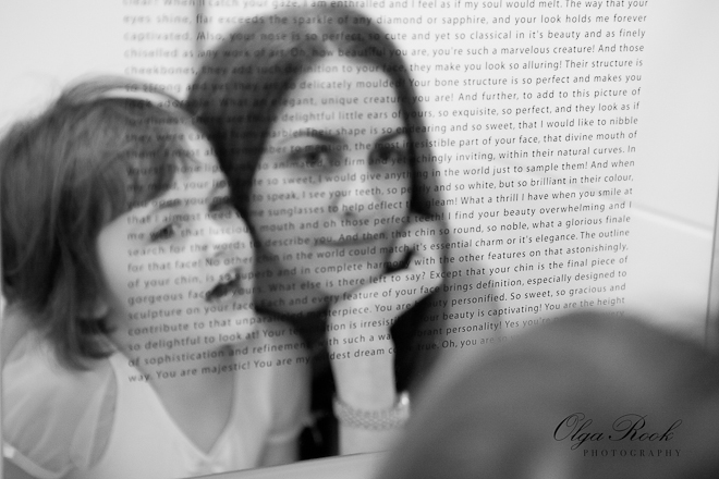 Black and white photo of a woman and a little girl looking in a mirror together. The mirror is not common: there is a text printed on it. It goes about liove and beauty and the mother and daughter are contemplating on it.