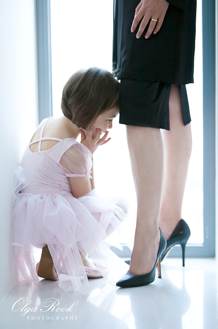 Portrait of a little girl wearing a ballet dress and looking with admiration at the legs of her mother on high heels.