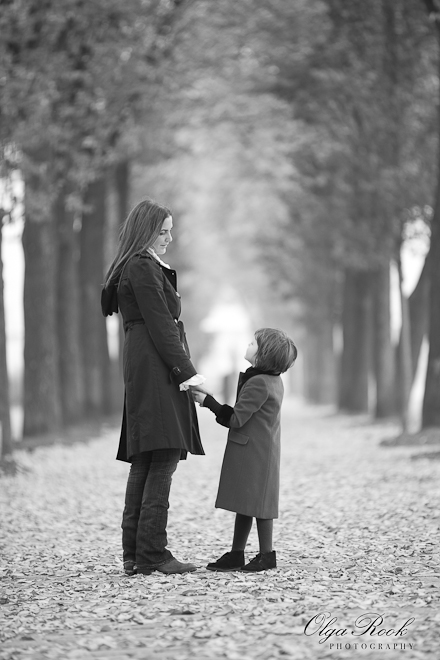 Black and white photo of a mother and a child walking in an autumn alley.