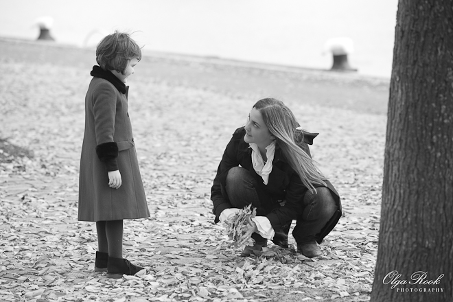 Photo of a woman collecting autumn leaves from the ground. Her little daughter is standing next to her trying to understand what will happen next.