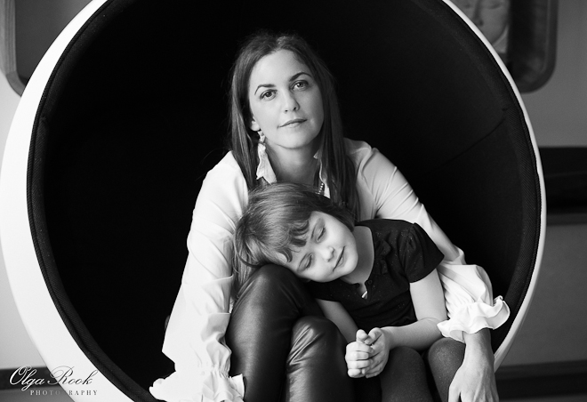 Portrait of a beautiful woman sitting with her little daughter in a round armchair (white from outside and black from inside). The little girl leans on her mother's knees with her eyes closed as if she is asleep.