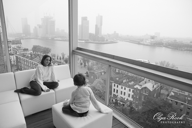 Black and white image of a mother and a daughter sitting on a balcony in a high tower and looking at Rotterdam from above. It is a misty morning the adds to the deramy atmosphere of the photograph.