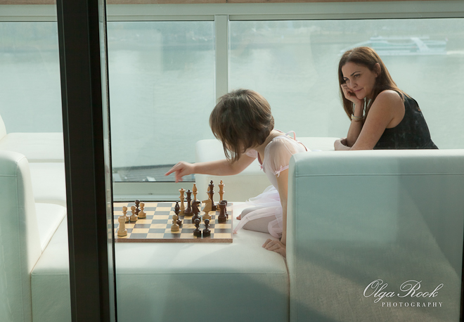 Atmospheric photograph of a little girl playing chess in a balcony and her mother observing her.