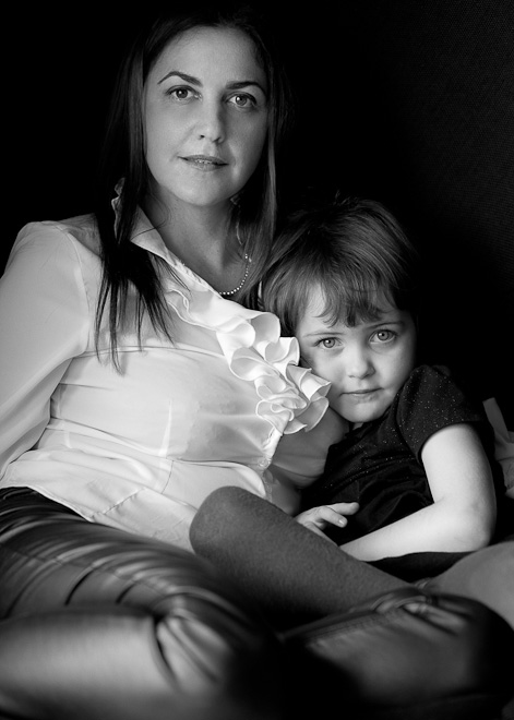 Nostalgic black and white portrait of a mother and her little daughter sitting together in a design armchair