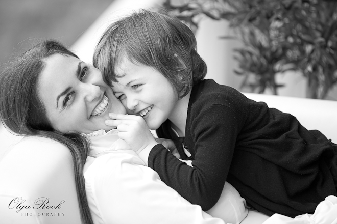 Black and white portrait of a little girl and her mother lying on a coach and laughing.