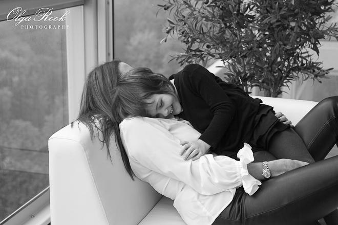 Photo of a mother and her little daughter huging and laughing on a blacony sofa.