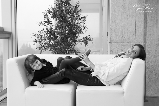 Photo of a mother and child playing and laughing on a sofa.