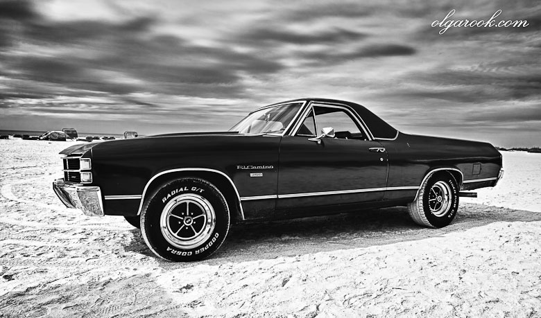 Dramatic black and white photo of a classic car on a beach in Florida.