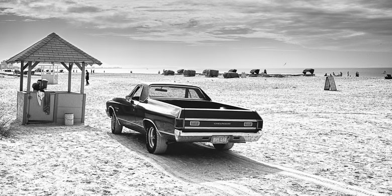 Black and white vintage style photo of a fancy old car in the middle of an almost empty beach.