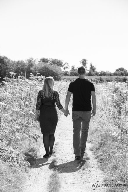 Photo of a romantic couple walking through a field on a summer day.