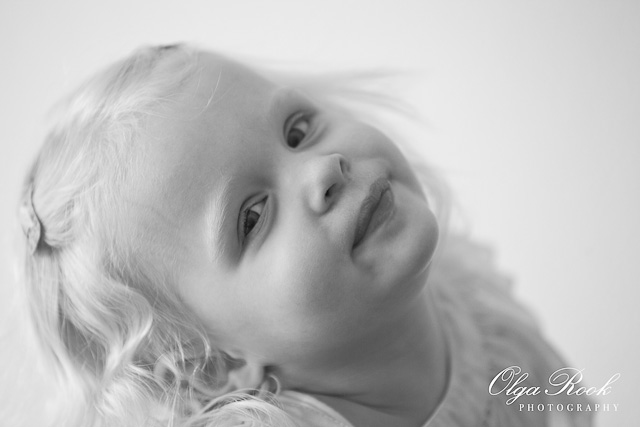 Photograph of a blond little girl with an impish smile