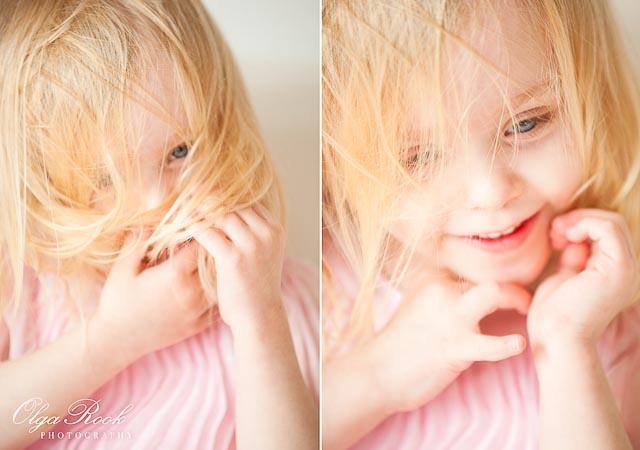 Portretten in pasterlkleuren: een klein lief meisje met haren voor haar gezicht.