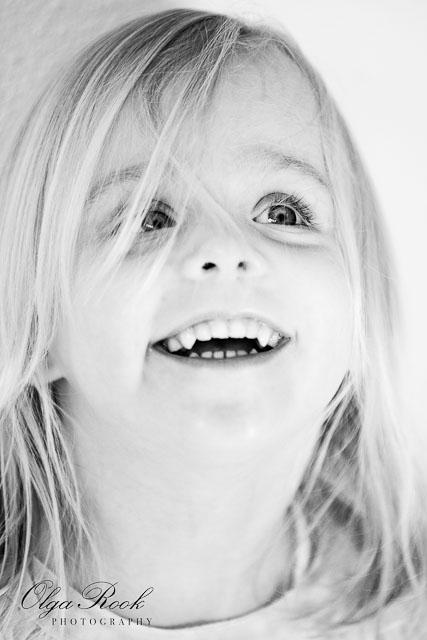 Zwartwit portret van een lachend meisje met spraknkelijnde ogen