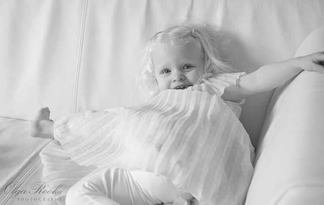 Foto van een lachend klein meisje: zij speelt op een bankje