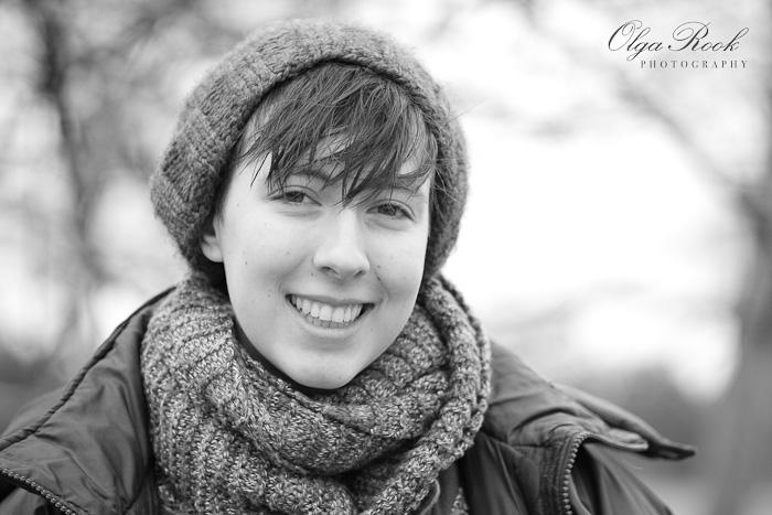 Zwartwit portret van een lachend meisje, die winterkleren draagt.